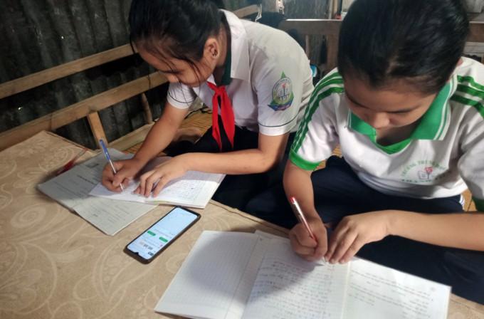 Hai chị em (lớp 6 và 8) cùng một nhà ở Cần Thơ học online chung trên điện thoại di động của mẹ. Ảnh: Đức Duy