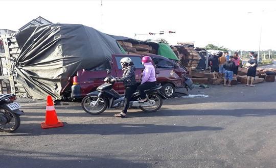 Xe container chở đầy gỗ đè bẹp xe con trên đường